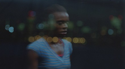 A woman watches from the night, lights reflected unfocused from a window