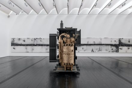 Front: Allora & Calzadilla, Blackout, 2020. Power transformer, bronze, electricity, vocalists, 120 1/2 × 85 1/2 × 78 3/4 inches. Courtesy of Lisson Gallery, New York and London. Rear: Allora & Calzadilla, Cadastre (Meter Number 18257262, Consumption Charge 36.9kWh x $0.02564, Rider FCA-Fuel Charge Adjusted 36.9 kWh x $0.053323, RiderPPCA-Purchase Power Charge Adjusted 36.9kWh x $0.016752, Rider CILTA-Municipalities Adjusted 36.9kWh x $0.002376, Rider SUBA subsidies $1.084), 2019. Iron filings on linen, overall: 72 × 840 inches, each: 72 × 120 inches. Courtesy of Gladstone Gallery, New York and Brussels. © Allora & Calzadilla. Photo: Paul Hester.
