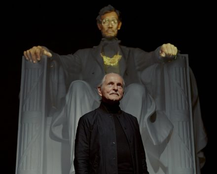 The artist Krzysztof Wodiczko at Galerie Lelong, next to a replica of the statue in the Lincoln Memorial. A video projects the faces and hands of Staten Island residents. Credit: Vincent Tullo for The New York Times