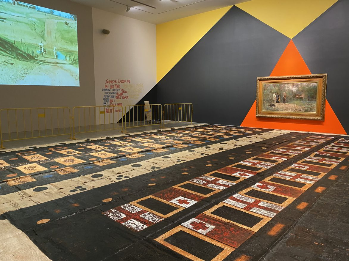 Exhibition view, NIRIN – the 22nd Biennale of Sydney, 2020, Museum of Contemporary Art, Sydney, Australia. Artworks in view: Eric Bridgeman, Rot Bung (Junction), 2019-20. Acrylic on wall, dimensions variable. Courtesy of the artist. Frederick McCubbin, A bush burial, 1890. Oil on canvas, 122.5 x 224.5cm. Courtesy of Geelong Gallery. Kulimoe'anga Stone Maka, Kuini Haati 2 (Two Queen Heart), 2008–10, and Togo mo Bolataane (Tonga and Britain), 2008–10. Oil, clay, daye on tapa cloth. Both 427 x 1115 cm. Courtesy of the artist. H.R. Balfourm Dendroglyphs of the Kalimangle Bora Ground, 1949. Single channel digital video from 16mm, colour, silent, 53 mins. Courtesy the Australian Institute of Aboriginal and Torres Strait Islander Studies. Brook Andrew, Powerful Object: Dendroglyph, 2020.3D model printed in clear filament, 109.5 x 49 x 23.5cm. Model made from a dendroglyph tree section, site marker, 19th Century. Collection of the Pitt Rivers Museum, University of Oxford [1948.12.77].
