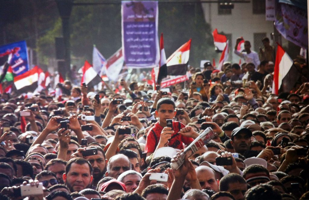 Image: Protesters during a speech in Tahrir Square, April 8, 2011. Photo by Mosa'ab Elshamy. © Mosa'ab Elshamy. Shared courtesy of Lara Baladi.