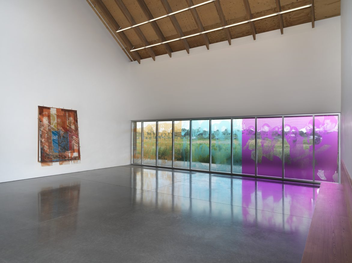 """Tomashi Jackson: The Land Claim. Installation view: Parrish Art Museum, Water Mill, NY, July 11–November 7, 2021. Left to right:  The Three Sisters, 2021. Collaborative Work: Vessels of Light (From Jeremy, Juni, and Steven), 2021. Pigmented, archival ink on polycarbonate sheets. Window installation with photographs by Jeremy Dennis; Richard """"Juni"""" Wingfield; and Juntos, New York, USA, 2020, by Steven Molina Contreras. Photo: Dario Lasagni"""
